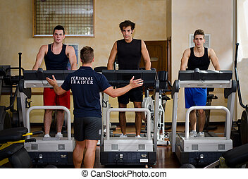 Three young men exercising on treadmills with personal trainer