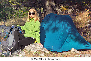 Young Woman with Smiling Face Hiker sitting with backpack...