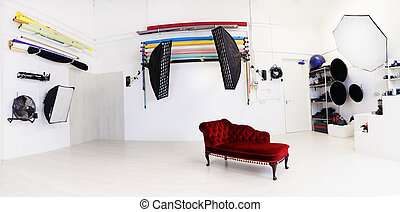 Interior of a photographic studio with a lone red sofa and...