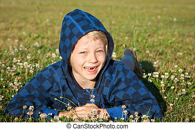 Happy boy lying in grass smiling