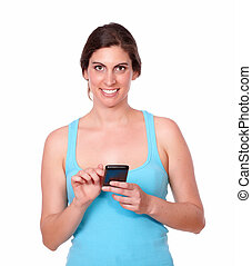 Smiling young woman texting on cellphone - Portrait of a...