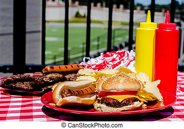 Tailgating party with cheeseburger, hot dog, potato chips,...