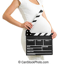 Pregnant woman hands holding clapper board on her belly
