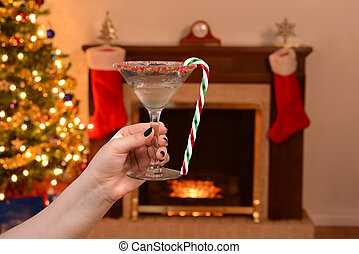 woman holding candy cane martini