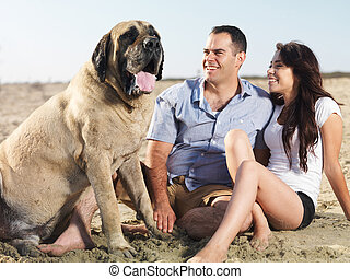 couple and pet dog enjoying time together on the beach