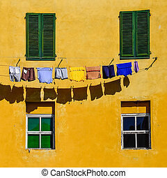 Detail of colorful yellow house walls, windows and clothes -...