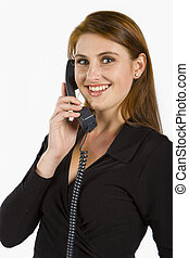 Communicating - Attractive lady talking on a phone against a...