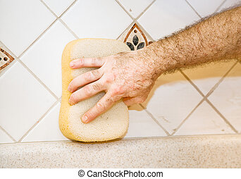 Tile Work - Wiping Grout - Worker\'s hand using a sponge to...