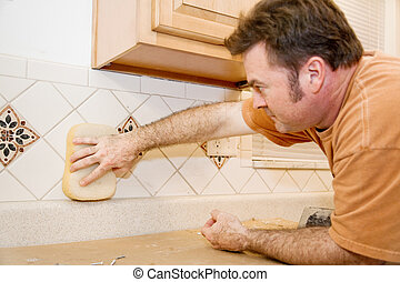 Tile Worker Wipes Grout - Tile worker wiping grout from a...