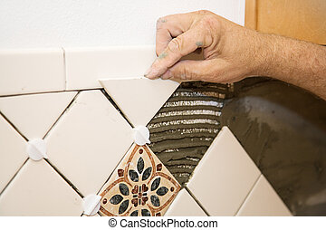 Setting Tile - Closeup of a tile setter\'s hand as he lays...