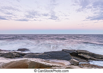 Waves crashing the ocean shore at crack of dawn Cape Breton,...