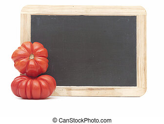 blank blackboard with two ripe tomatoes isolated on white background.