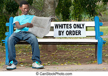Racial discrimination - A non-white man sits on a bench in a...