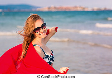 Beautiful woman with red scarf on the beach. Travel and...