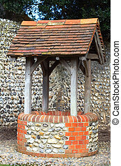 wishing well - A old wishing well with a brick wall behind...