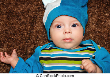 Blue-eyed baby lies on his back and smiling while looking at...
