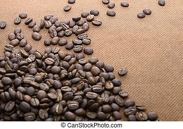 Heaps of offee beans on grung wooden board background