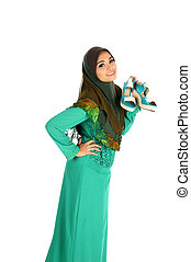 Pretty young Asian Muslim woman posses shopping with shoe action. Islamic fashionable attire concept