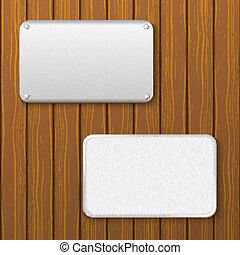 Two metal plates on a wooden wall