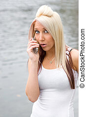 Surprising Call - An attractive blonde woman has a surprised...