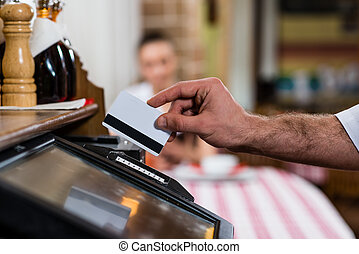 waiter inserts the card into a computer terminal, against...