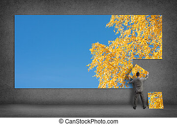 businessman collects the image of blue sky and yellow leaves