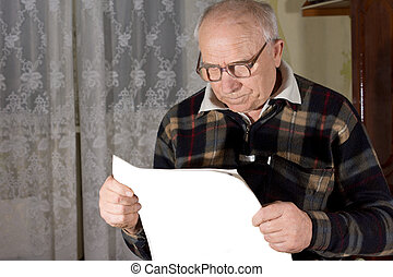 Senior man wearing reading glasses looking at a newspaper...