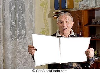 Elderly male pensioner reading a newspaper with a look of...
