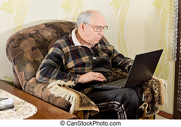 Elderly man surfing the internet on a laptop - Elderly man...
