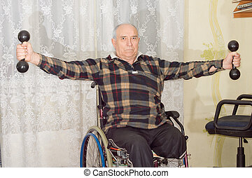 Disabled man working out with dumbbells - Disabled senior...