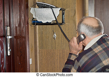Elderly man talking on a telephone sitting with his back to...