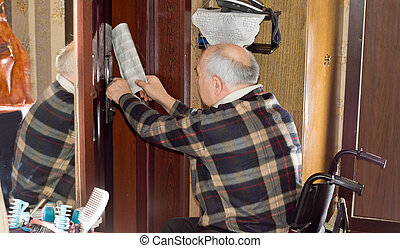 Senior man retrieving a newspaper through a door - Senior...