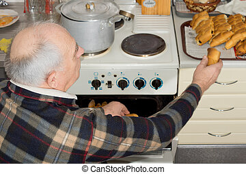 Senior man taking a bread roll out of the oven in the...