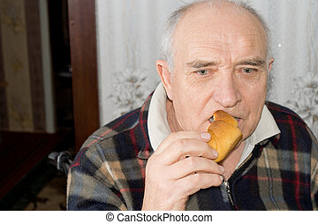 Elderly pensive man eating a bread roll - Elderly pensive...