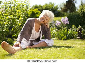 Happy senior woman sitting relaxed in garden