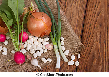 onion, radishes, beans, garlic on a wooden table