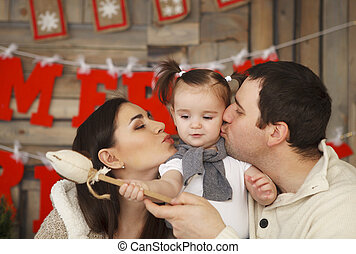 Happy smiling family with one year daughter near the...