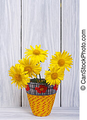 Yellow daisies in a vase on a wooden background