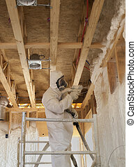 Close up of a worker blowing insulation - Close-up of a...