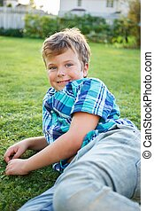 Positive young boy lying on a meadow