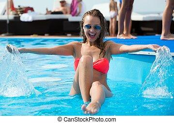 Sexy young girl having fun in a pool