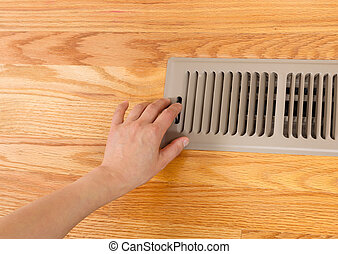 Opening up Floor Vent Heater - Horizontal photo of female...