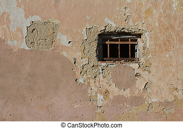 old small window with bars in a wall covered with plaster