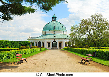 Baroque pavillon with a footpath and park benches in...