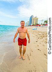 man enjoys walking along the beach