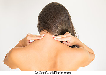 Woman with upper back and neck pain standing naked with her...