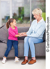 senior grandma playing with granddaughter - cheerful senior...