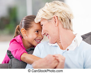 cute little girl hugging grandma at home