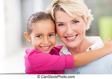 young girl hugging her senior grandmother - beautiful young...