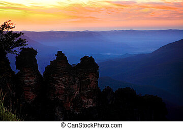 Just the three of us.  The dramatic  sunrise on a spring morning against the silhouetted iconic landmark, The Three Sisters, at Echo Point, Blue Mountains, Australia.  Image has some grain.